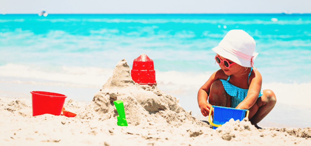 Young girl building a sandcastle - Dental Services for Children
