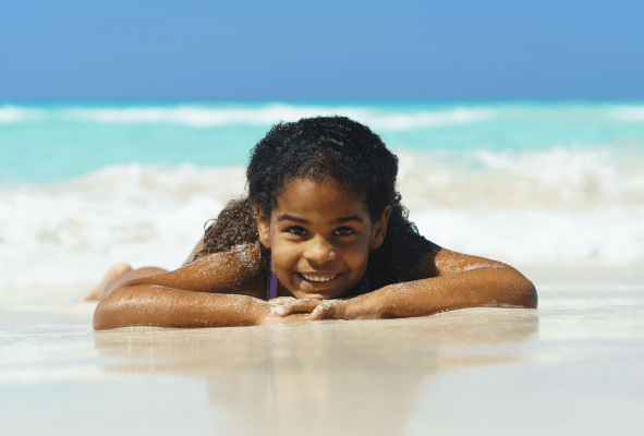 Young Girl laying on beach smiling - Children's Dental Health